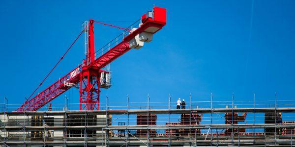 Rode kraan bij bouwwerk.klein